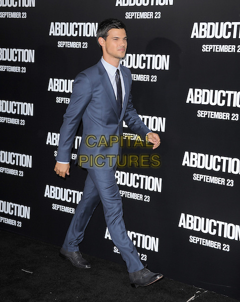 "Taylor Lautner.The Premiere of ""Abduction""  held at The Grauman's Chinese Theatre in Hollywood, California, USA..September 15th, 2011.full length black tie white shirt blue suit walking side profile .CAP/RKE/DVS.©DVS/RockinExposures/Capital Pictures."