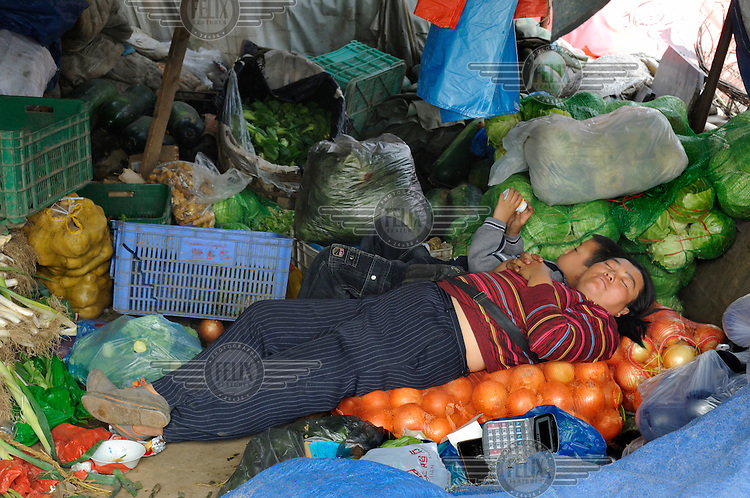 Market seller sleeping at her stall on top of a pile of onions whilst her son amuses himself by her side.