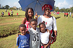 Independence Day, Trinidadian mother and children with umbrella on the Savannah, Port of Spain