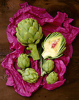 Agriculture - Produce, various sized artichokes on tissue paper and barnwood, with one artichoke cut in half.
