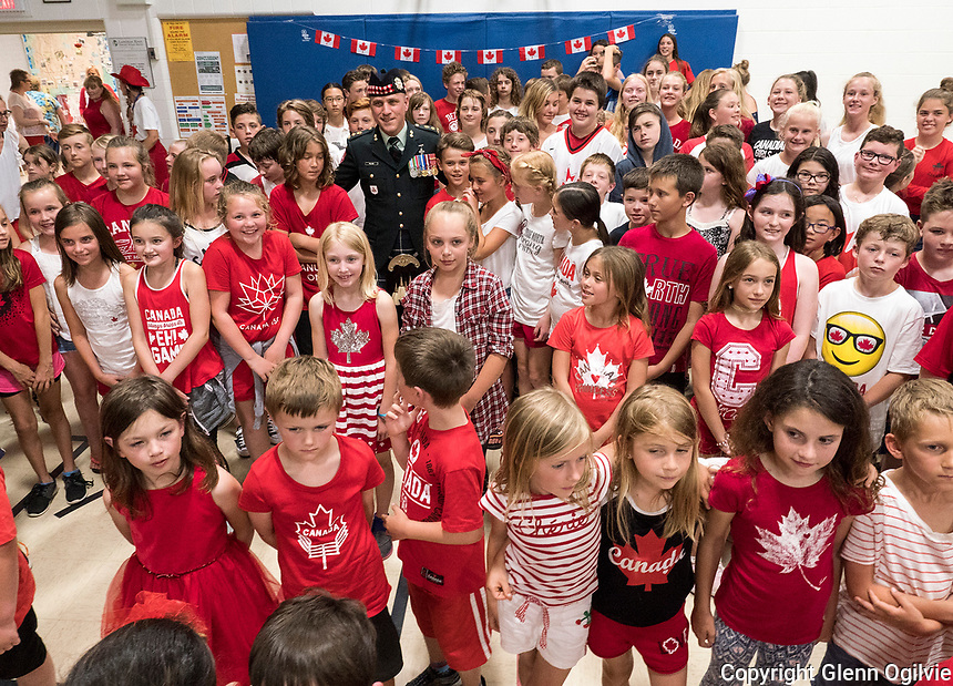 Errol Village Public School Home and School Association held an official opening of the  Brent Poland Memorial Playground, Friday, June 23. Here, Brent's brother Lieutenant Colonel Mark Poland  meets with students who were all decked out in Canada colours for the ceremony.