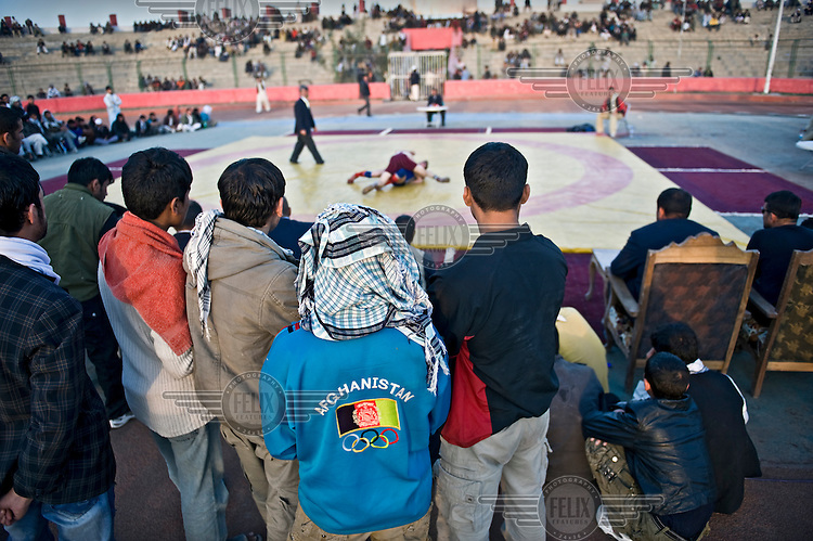 Spectators watch a match at the Olympic Stadium in Kabul, where the national wrestling championship is taking place. Young men from across the provinces have come to Kabul to participate.