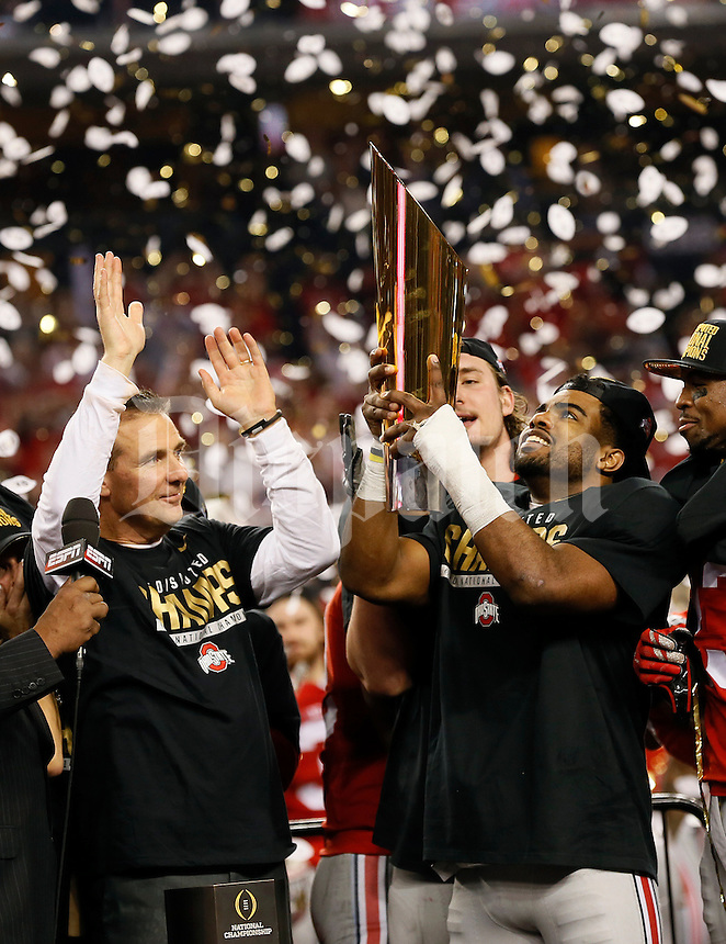 Ohio State Buckeyes head coach Urban Meyer watches as running back Ezekiel Elliott (15) hoists the trophy following their 42-20 win over Oregon in the College Football Playoff National Championship at AT&T Stadium in Arlington, Texas on Jan. 12, 2015. (Adam Cairns / The Columbus Dispatch)