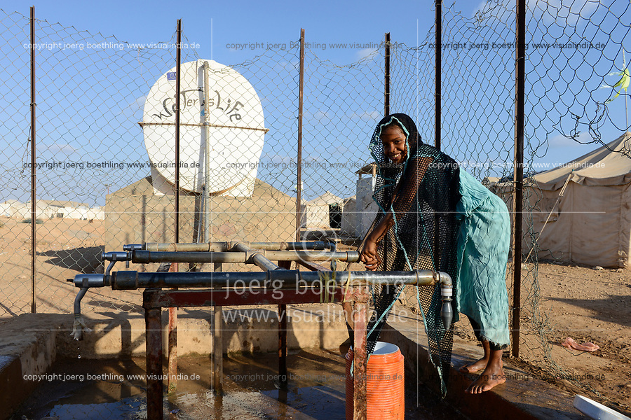 DJIBOUTI , Obock, refugee camp Markazi for yemeni war refugees, girl fetch water from tap, slogan water is life written on tank / DSCHIBUTI, Obock, Fluechtlingslager Markazi fuer jemenitische Fluechtlinge, Wasserstelle