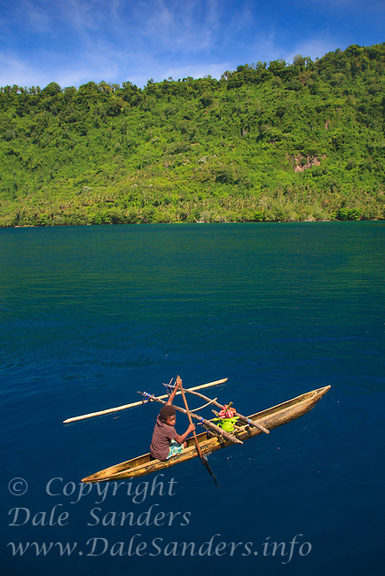 In the Witu Islands off New Britain Island in Papua New Guinea, young children learn to paddle an outrigger canoe almost before they can walk. This young boy paddles his outrigger canoe inside the flooded crater of an ancient volcano on Garove Island.