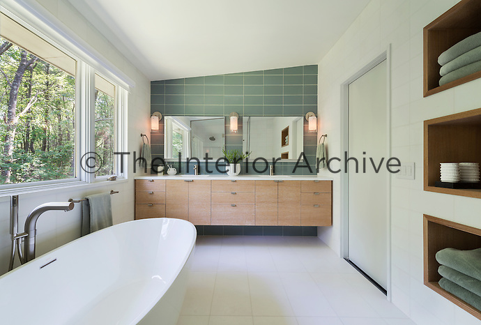 A contemporary white tiled bathroom with a free-standing bath placed below a window. Two mirrors hang on a grey tiled wall above two washbasins, which are set in a wall-mounted storage unit. Folded towels are stored neatly in a recessed shelving unit.