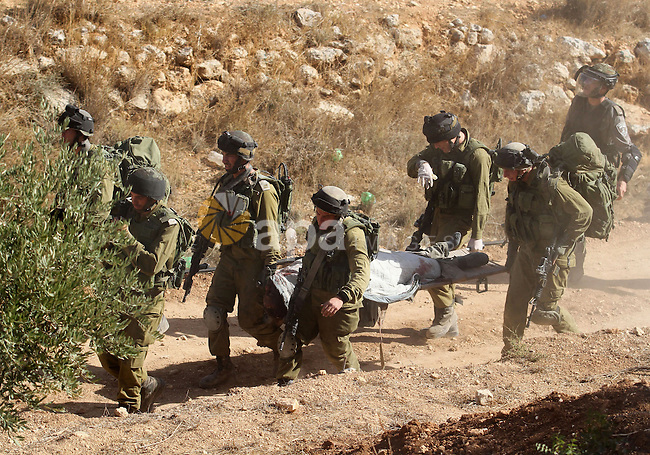 Israeli soldiers carry away the body of armed Palestinian militant Mohammed Assi near the West Bank village of Bilin, near Ramallah October 22, 2013. Israeli forces on Tuesday killed Assi, 28, who was wanted for his alleged involvement in a Tel Aviv bus bombing last year, Israel's Shin Bet security service said. The Islamic Jihad group said Assi was one of its members. Photo by Issam Rimawi