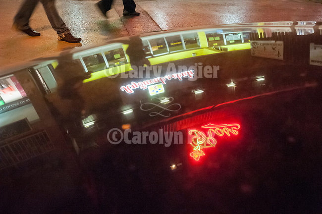 Reflections of lights and neon of the Rose Hotel on  the hood of an automobile at night, Serbia