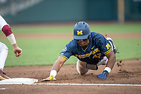 Michigan Wolverines designated hitter Jordan Nwogu (42) dives back to first base during Game 6 of the NCAA College World Series against the Florida State Seminoles on June 17, 2019 at TD Ameritrade Park in Omaha, Nebraska. Michigan defeated Florida State 2-0. (Andrew Woolley/Four Seam Images)