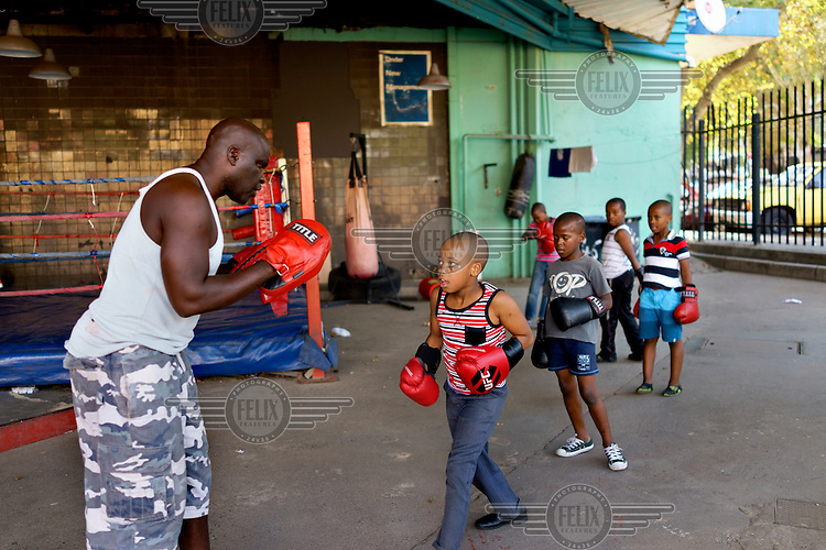 Children sparring with George Khosi at an after-school training session at the Hillbrow Boxing Club. After gunshot injuries put an end to his own boxing career, George Khosi founded the club to instil discipline, camaraderie and an activity away from the streets for young people from the community, and also to provide a training space for upcoming professional boxers. The club operates in a donated space on the forecourt of a disused petrol station in Hillbrow, one of the country's most notorious neighbourhoods.