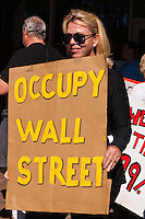 "A woman holds an ""Occupy Wall Street"" sign in front of another woman holding a ""We are the 99%"" sign during the Occupy Orange County, Irvine march on November 5.  This picture was taken in front of an Irvine Bank of America branch."