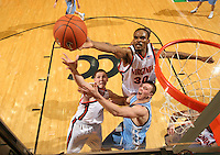 Virginia's Adrian Joseph (30) reaches for the rebound over teamate Laurynus Mikalauskas and North Carolina's Tyler Hansbrough during a college basketball game Thursday, Jan. 19, 2006, at University Hall in Charlottesville, Va. Virginia won 72-68. (Photo/Andrew Shurtleff)..win celebrate victory