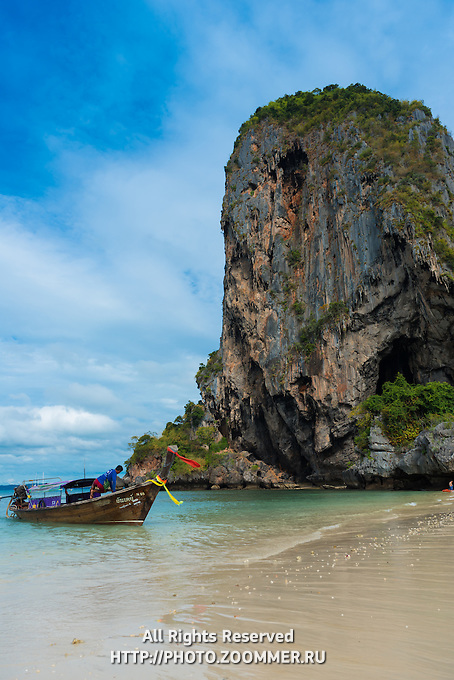 Longtail boat near a rock on Phra Nang beach in Krabi, Thailand