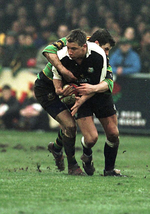 Photo. Richard Lane. .Northampton v London Irish. 29/1/99. .Justin Bishop is tackled by Paul Grayson as he attacks.