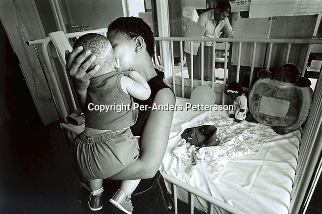 CAPE TOWN, SOUTH AFRICA - FEBRUARY 11: Patricia Lincoln, age 16, comforting her one year old daughter Baby Thsepang as she is recovering on February 11, 2002 at the Red Cross ChildrenÕs Hospital in Cape Town, South Africa. The baby was brutally raped by her father in October in Loisevale, a poor colored area outside Upington, about 900 kilometers Northwest of Cape Town, South Africa. The country is struggling with increasing number of rapes and sexual abuse of young children and the country has the highest number of rapes in the world..(Photo: Per-Anders Pettersson/Getty Images).