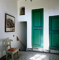 The landing area has green painted doors and black and white check pattern floor tiles. A decorative chair stands on one side.
