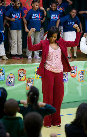 21 Apr 2010, Washington, DC, USA --- First lady Michelle Obama shows off her muscles along with the children at the DC River Terrace School at an event to promote physical fitness and her Let's Move campaign in Washington --- Image by © Brooks Kraft/Corbis