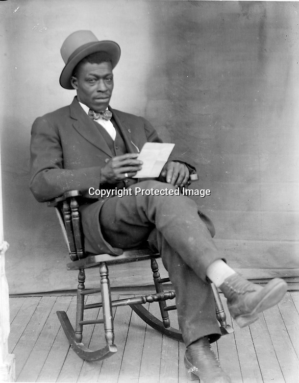 YOUNG MAN IN ROCKER<br /> The simple prop of a piece of paper gives this portrait a sense of alertness or anticipation, despite the man's relaxed pose, tilting back his rocking chair. A backdrop is artfully placed to bring out details and forms.<br /> <br /> Photographs taken on black and white glass negatives by African American photographer(s) John Johnson and Earl McWilliams from 1910 to 1925 in Lincoln, Nebraska. Douglas Keister has 280 5x7 glass negatives taken by these photographers. Larger scans available on request.