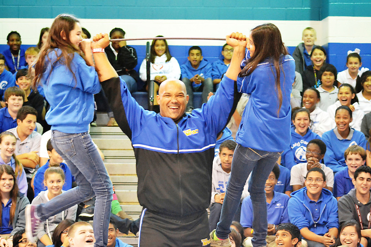 Stephen Mackey of &ldquo;Team Impact&rdquo;&mdash;a group that encourages kids to work hard and believe in themselves through displays of strength&mdash;lifts Pin Oak Middle School students Madeline Ashcroft and Noor Malik using a makeshift barbell. During their shows, Mackey and his team of 19 use their strength to rip phone books in half, break wooden bats over their knees and bend iron rods into neat little ties.<br /> To submit photos for inclusion in eNews, send them to hisdphotos@yahoo.com.