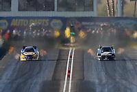 Feb. 23, 2013; Chandler, AZ, USA; NHRA funny car driver Cruz Pedregon (right) races alongside Ron Capps during qualifying for the Arizona Nationals at Firebird International Raceway. Mandatory Credit: Mark J. Rebilas-