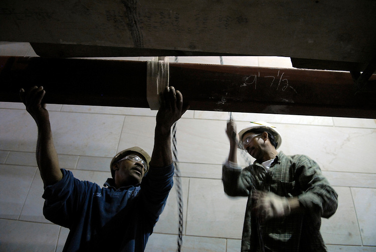 Otis Devese, left, and Manuel Guebara hoist a steel beam on the site of the Capitol Visitor Center.