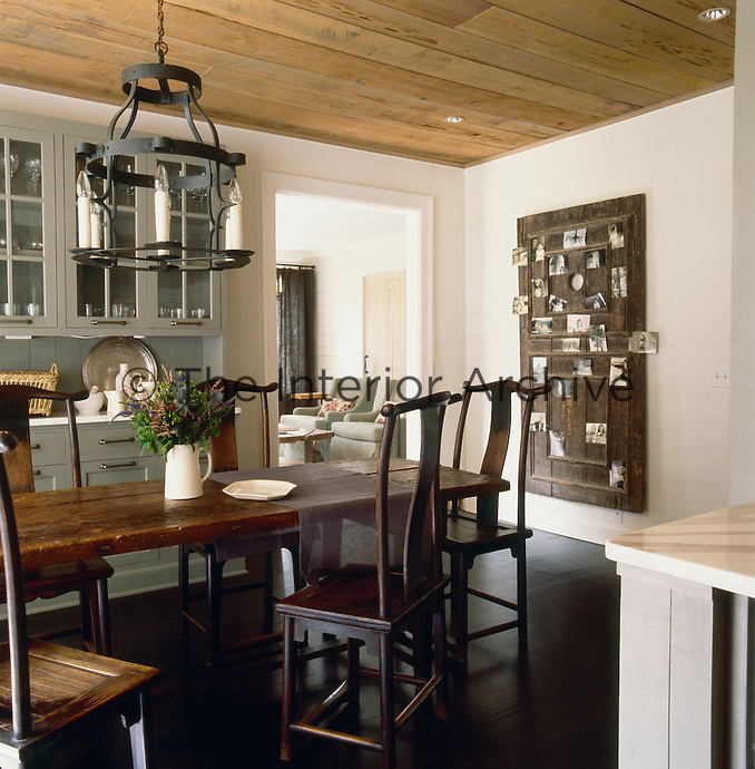 An old Southern door serves as both a picturesque focal point and a family photo album in this clean-lined dining room