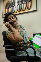 Dr. Nayana Patel, tends to a phone call as she dictates her email answers to her assistant in her Akanksha IVF and surrogacy center in Anand, Gujarat, India on 10th December 2012. Surrogacy clients pour into Anand from across the world pursuing Dr Patel's expertise on the process, and they keep in touch with her and the progress of the pregnancies via the internet and phone. While 15% of couples are infertile globally, only 6% of infertility cases require surrogacy as a last option. Photo by Suzanne Lee / Marie-Claire France