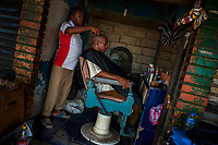 A Colombian hairdresser cuts a man's hair in a barber shop in the market of Bazurto, Cartagena, Colombia, 17 April 2018.