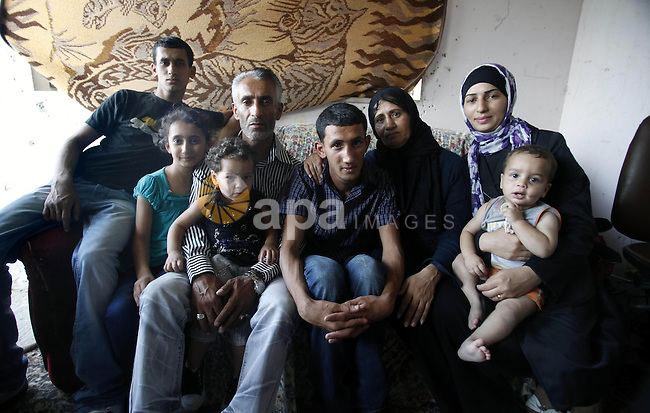 Ahmed Obaid (C), 18, a mentally disabled Palestinian youth, sits with his family at their home in Issawiya neighborhood in Jerusalem on 02 September 2013. Israeli security forces arrested Obaid during a protest against killing of three Palestinians in Qalandiya refugee camp. He was released on bail on Monday after spending a week in jail under torture. Photo by Saeed Qaq
