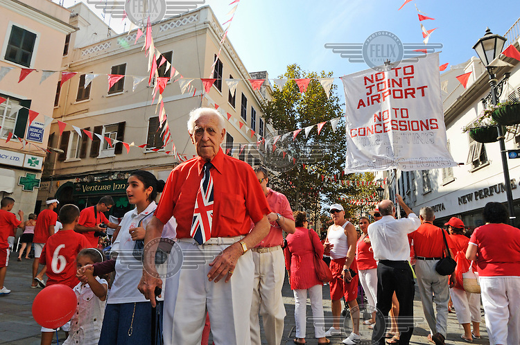 An elderly man sporting a union jack tie walks among crowds of Gibraltarians celebrating on Main Street during Gibraltar National Day.