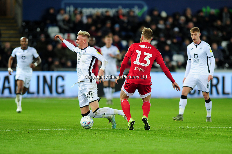 Sam Surridge of Swansea City is fouled by Tim Ream of Fulham during the Sky Bet Championship match between Swansea City and Fulham at the Liberty Stadium in Swansea, Wales, UK. Friday 29 November 2019