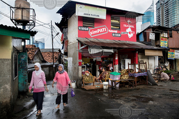 Two women walk past a small shop.