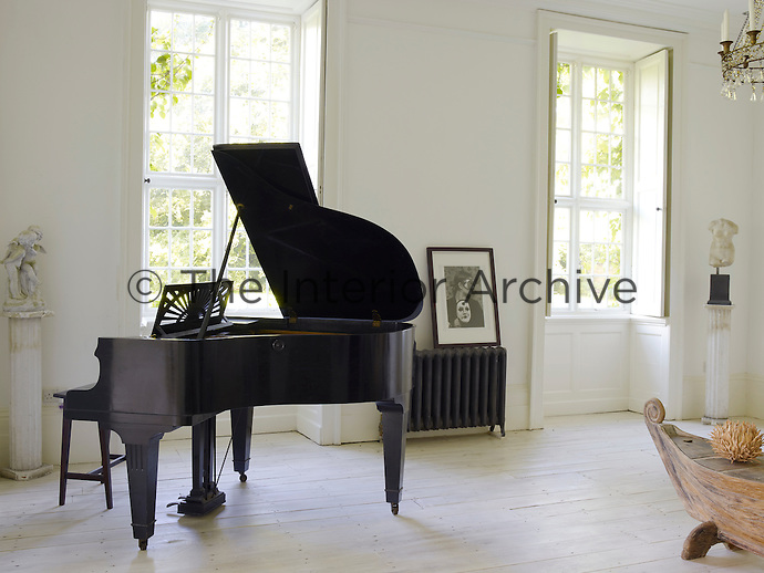In the living room the polished surface of a grand piano gleams against the chalk white walls and lime washed floorboards