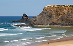 Surfers on Atlantic Ocean waves breaking on rocky headland and bay with wide sandy beach, surfer and a few sunbathers, Praia de Odeceixe, Algarve, Portugal, Southern Europe