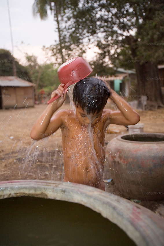 Sarak washing himself with a bucket and cold water before going to bed..Sarak is a young Khmer boy who comes from a peasant family, living in a small village in Battambang Province, in northwest Cambodia. He lives with his mother and father, brothers, sister, cousins and his aunts and uncles. they are a big family. Sarak loves to learn how to be an acrobat in the local circus school, and spends as much time as he can doing headstands and somersaults with his friends. To be honest, he is a bit of a scoundrel, and enjoys head butting the billy goat, but he makes up by feeding all the animals in his parents little farm. His mother works at the fishmarket in Battambang town, whilst his father sells icecreams. They don't have very much money, not even electricity, so he and his brothers and sisters do their homework under candlelight. He likes to take trips, with his mother and cousins, on his uncle's scooter.
