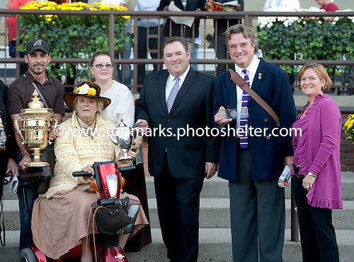 Phyllis Wyeth, seated, poses with Champagne Stakes trophy following Union Rags' win. Second from right is her husband, noted artist Jamie Wyeth.