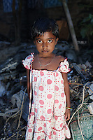 In the village of Sangrampur, a young girl stands amongst electronic waste, collected for recycling and reselling in nearby Kolkata, India. November, 2013