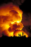 Gas well blowout and fire with workers in silhouette.