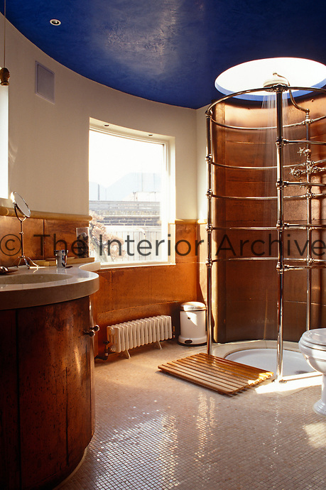 The walls of this curved shower room have been lined with copper and the floor laid with small mosaic tiles