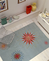 A bright and cheerful woollen rug with geometric and floral motifs covers this living room floor