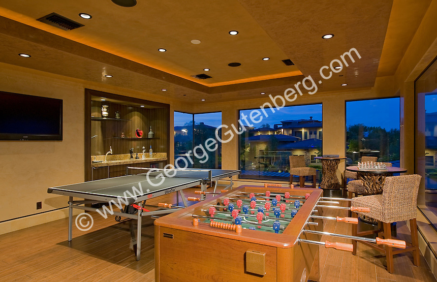 Large game room with wetbar and table games seen at night