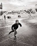 USA, Oregon, Portland, boy running on street with fountains in the background (B&W)