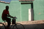 Cuba, Trinidad: World Heritage Site: boy on bike against gaily, green painted house, white door, Caribbean,