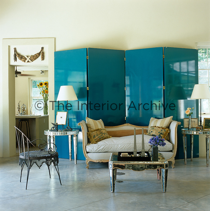 The large blue-lacquer screen creates a focal point and is a striking backdrop for a collection of antique furniture and objects including an 18th-century sofa