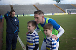 Home team forward Declan McManus poses for a photograph with two young mascots on the pitch before Greenock Morton take on Stranraer in a Scottish League One match at Cappielow Park, Greenock. The match was between the top two teams in Scotland's third tier, with Morton winning by two goals to nil. The attendance was 1,921, above average for Morton's games during the 2014-15 season so far.