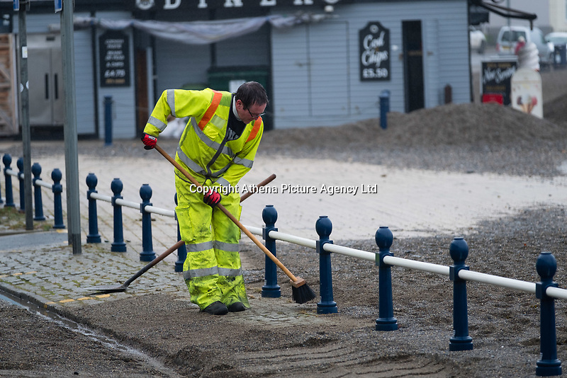 """Pictured: Council workers clear debris off the promenade of the seaside town of Aberystwyth, Wales, UK. Monday 23 October 2017<br /> Re: A clean operation is under way at coastal parts of the UK were affected by Storm Brian.<br /> Roads in Aberystwyth's seafront and at nearby Aberaeron, Wales were shut on Saturday morning as a yellow """"be aware"""" Met Office warning is in place."""