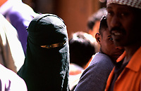 Yemen,Young veiled girl in a crowd of men in Sana'a