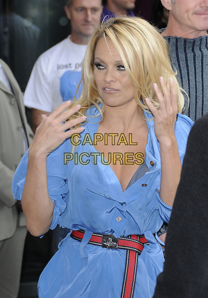 PAMELA ANDERSON.Attends a photocall for PETA at the .London Transport Museum, Covent garden, London, England, UK, .October 24, 2010..half length blue shirt belt red dress Vivienne Westwood hands gesture .CAP/CAN.©Can Nguyen/Capital Pictures.