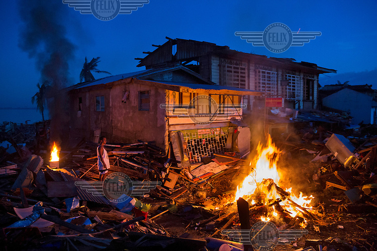 A man stands by a fire next to a house damaged by Typhoon Hayan in the city of Tacloban which was badly affected by the storm. Typhoon Haiyan, or Typhoon Yolanda as it is known in the Philippines,  was the deadliest typhoon to hit the Philippines to date and is known to have killed over 5,700 people. It made landfall on 7 November 2013 and reached wind speeds of over 140 miles per hour.
