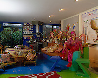 Portrait of fashion designer Zandra Rhodes sitting in her colourful open-plan living area